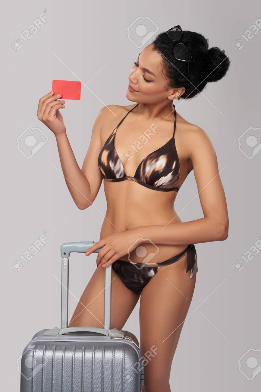 20b904d24e Fashionable beautiful mixed race african american - caucasian woman in brown  swimsuit standing with travel suitcase