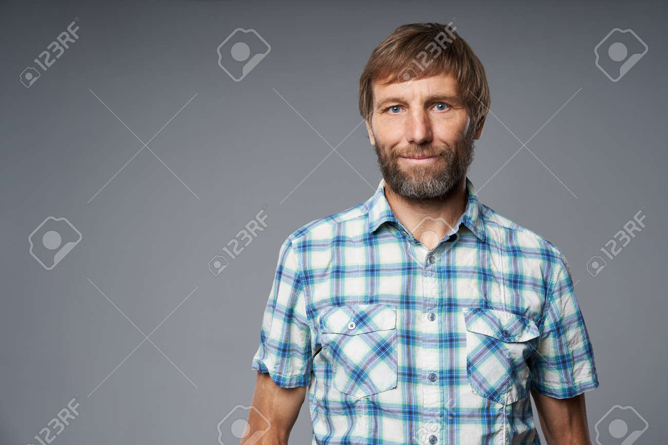Portrait of mature man in checkered shirt looking at camera, over grey studio background - 120778657