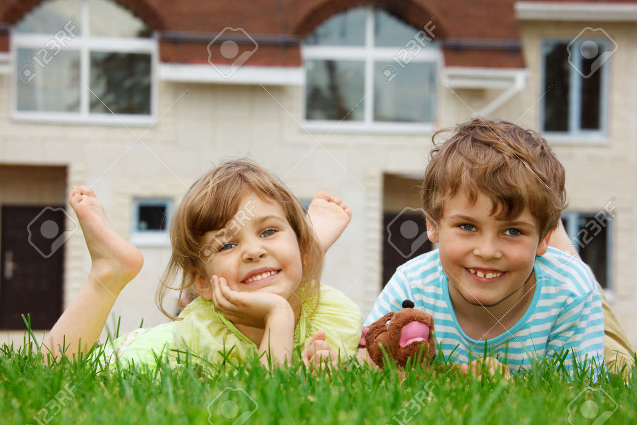 Smiling brother and sister lying on lawn in front of new home. In hands of boy toy. Stock Photo - 11723106