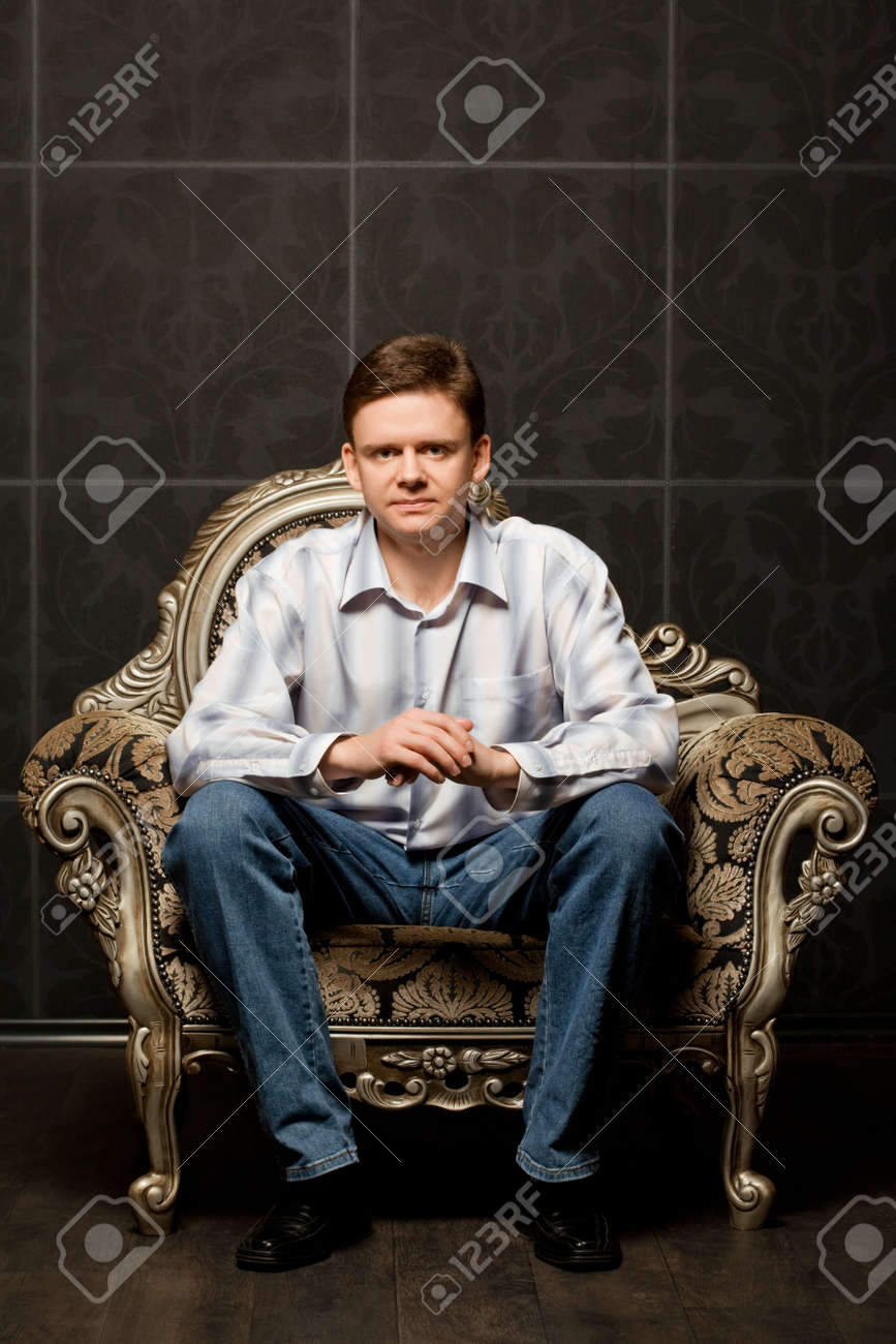 young man sitting in magnificent ancient armchair Stock Photo - 12136229