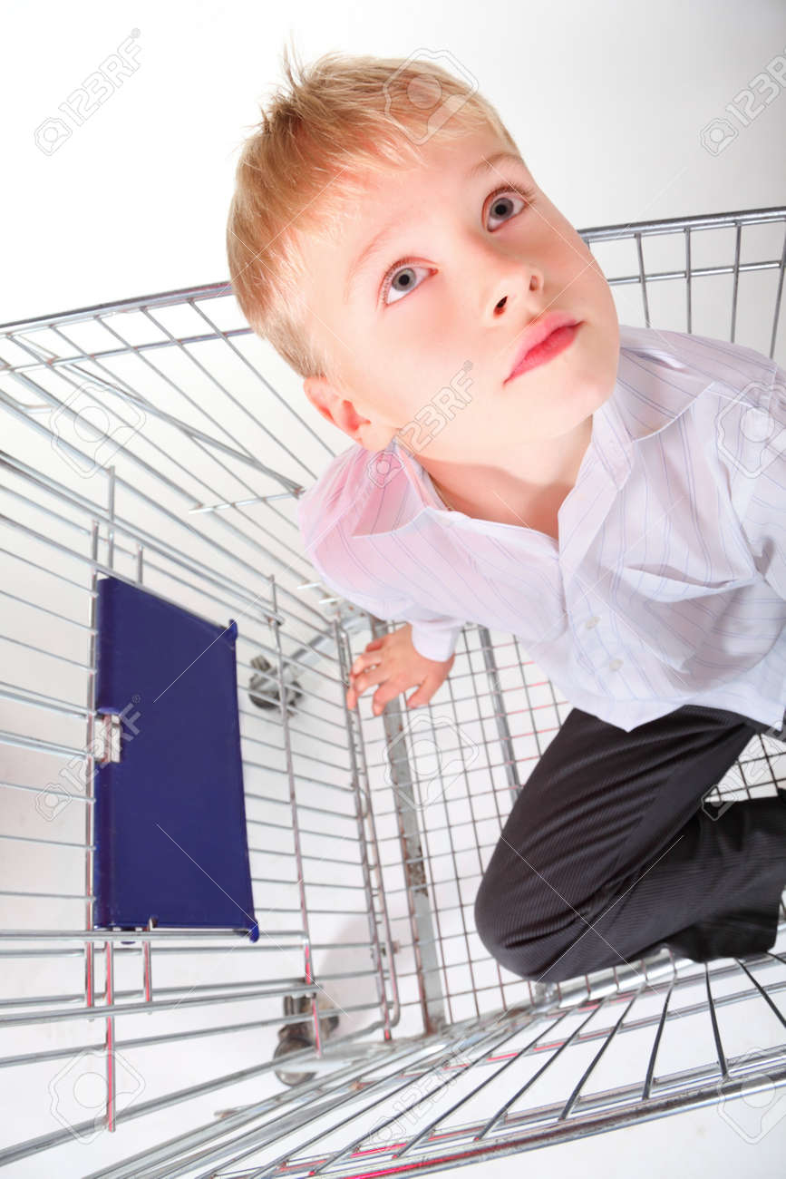 little boy is sitting in shoping basket and looking away. isolated. Stock Photo - 12130847