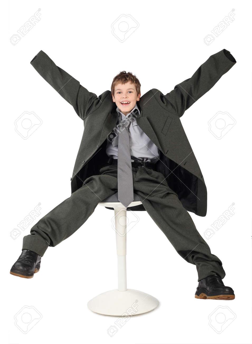 c238d175a5f Foto de archivo - Niño pequeño en traje de hombre gris grande que se sienta  en la silla y sonriendo aisladas sobre fondo blanco