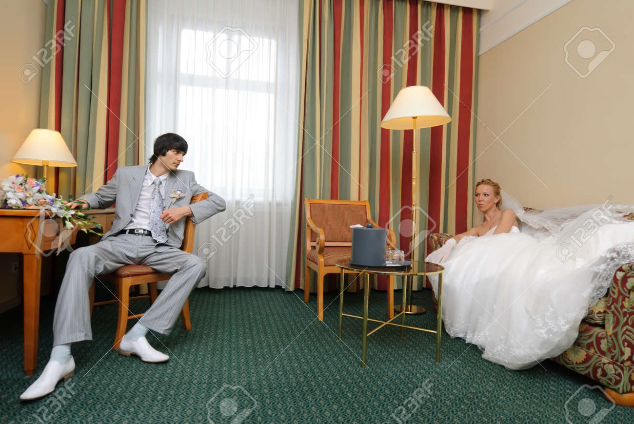 Bride and groom in hotel room looking at each other. Stock Photo - 12734199
