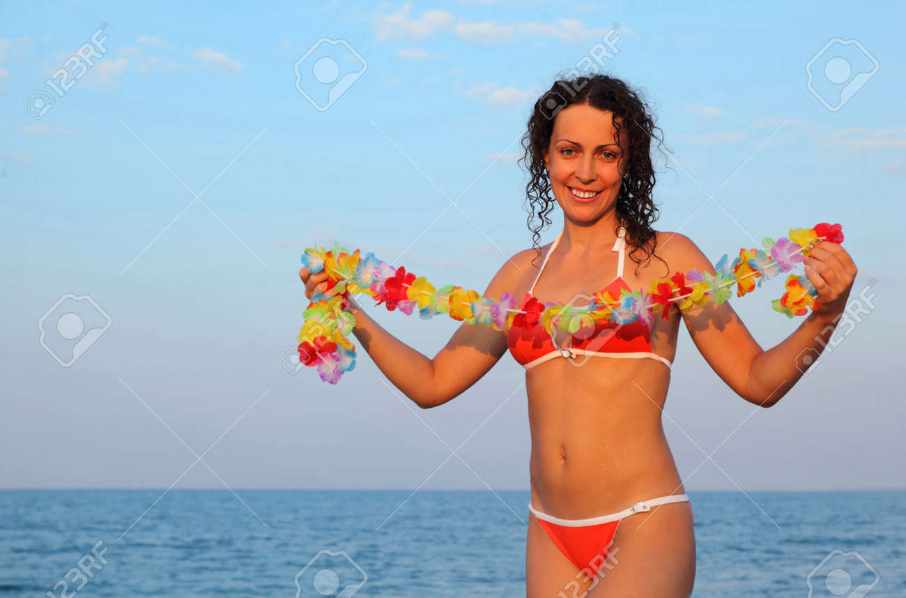 Beautiful young woman dressed in bathing suit holding garland beautiful young woman dressed in bathing suit holding garland of hawaiian flower and stands on beach izmirmasajfo