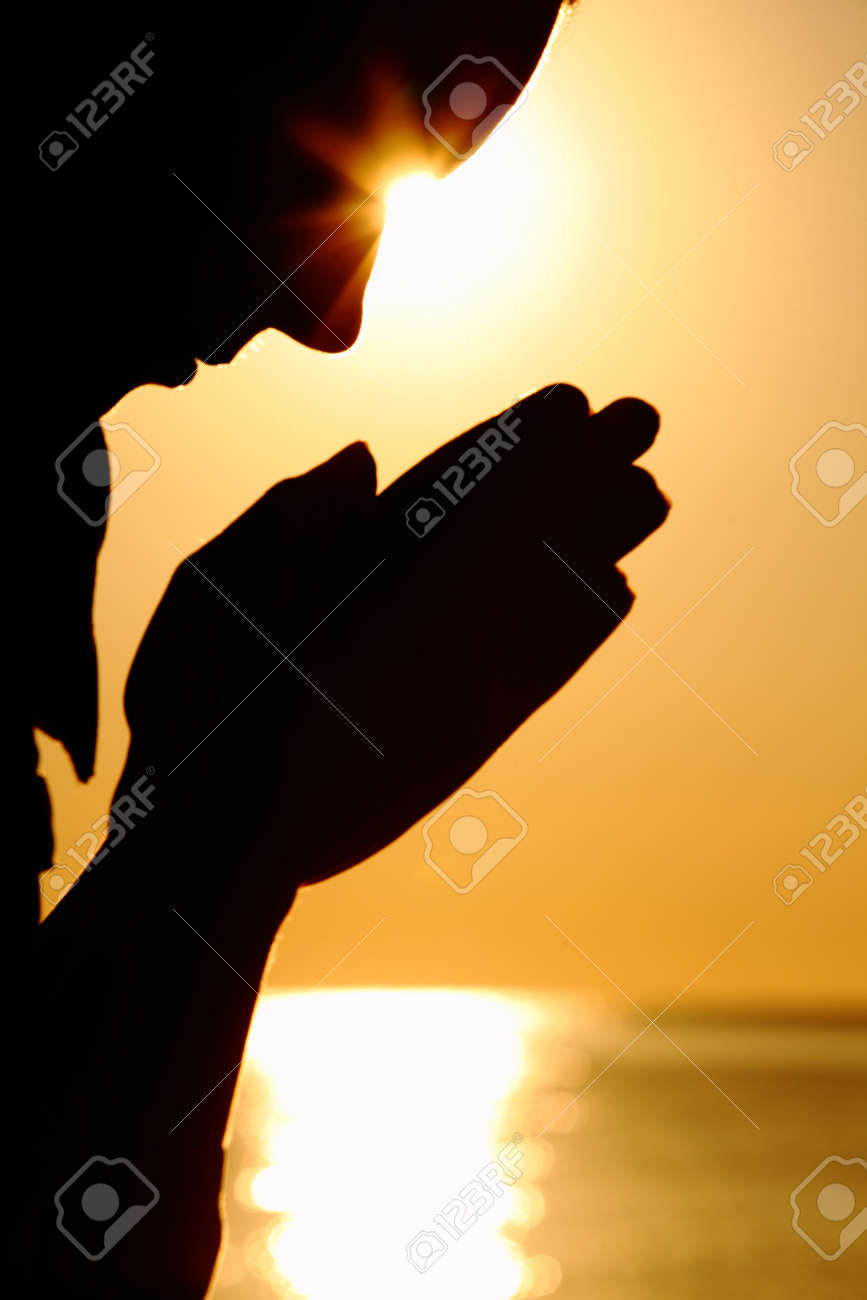 Silhouette of woman which sits near  sea opposite  sun and laid down hands before itself and prays Stock Photo - 12510119