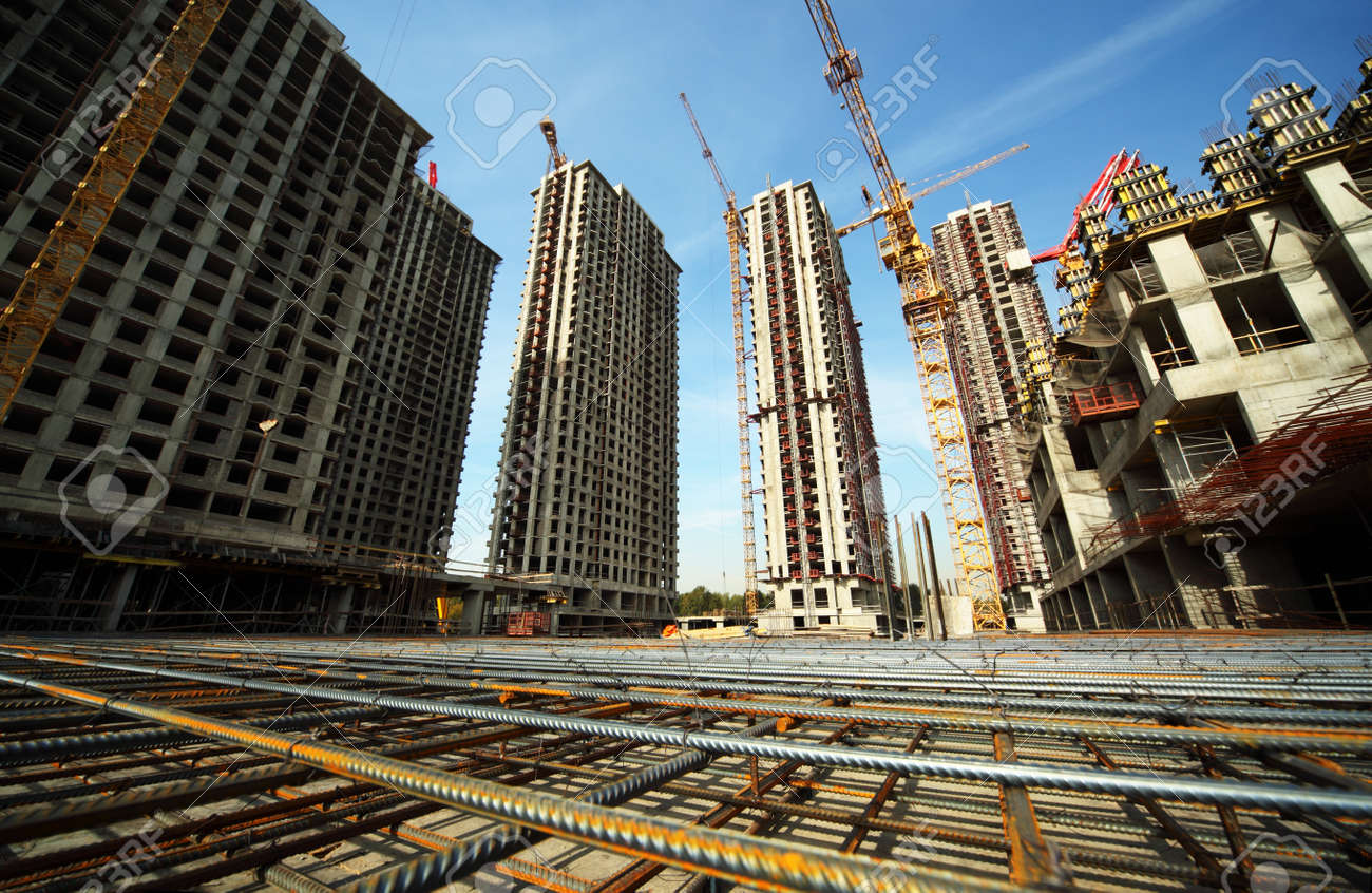 Between tall buildings under construction and cranes under a blue sky Stock Photo - 12512559