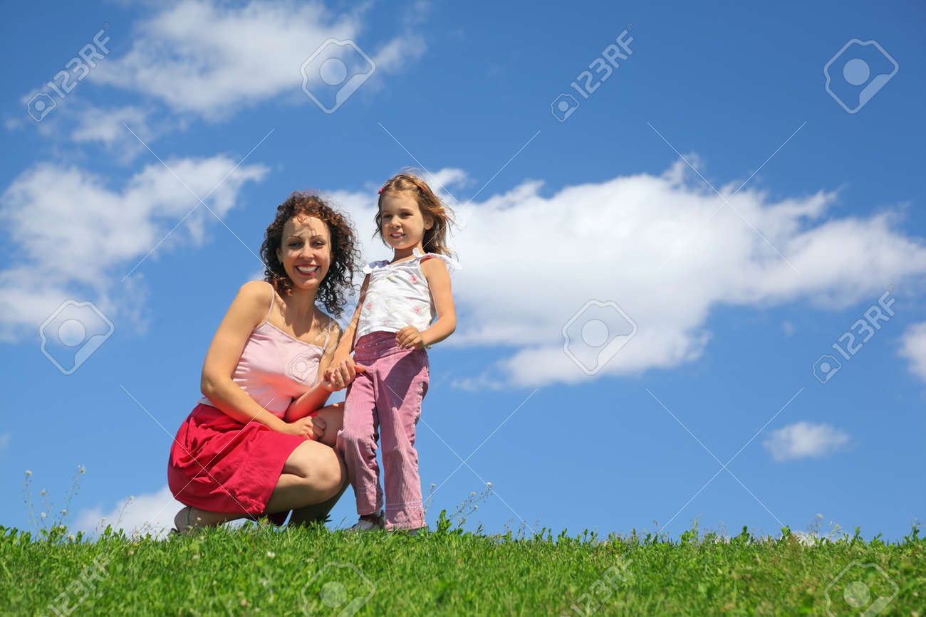 Mother squatting alongside with daughter holds it for hand and laughs Stock Photo - 12646434