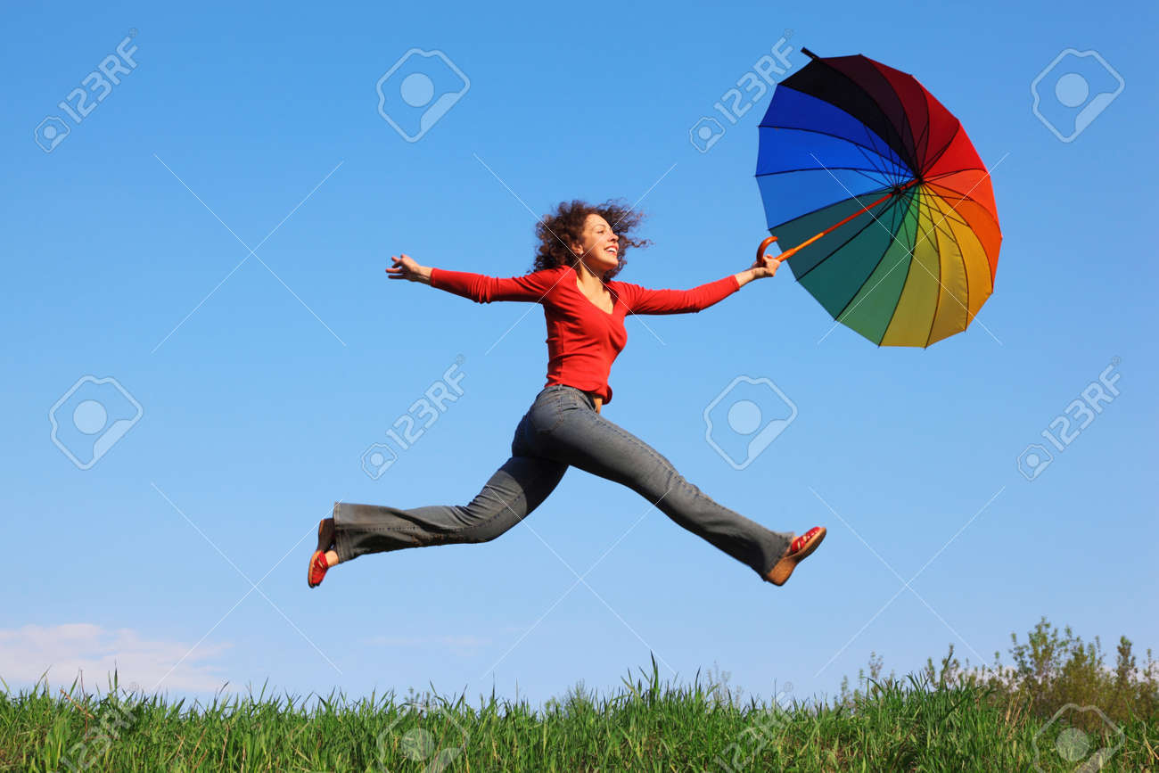 Girl jumping over green grass with colorful umbrella in his hand against blue sky Stock Photo - 12647136