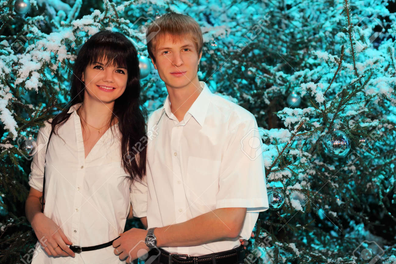Young man and woman wearing white shirts stand near green trees in snow Stock Photo - 17733466