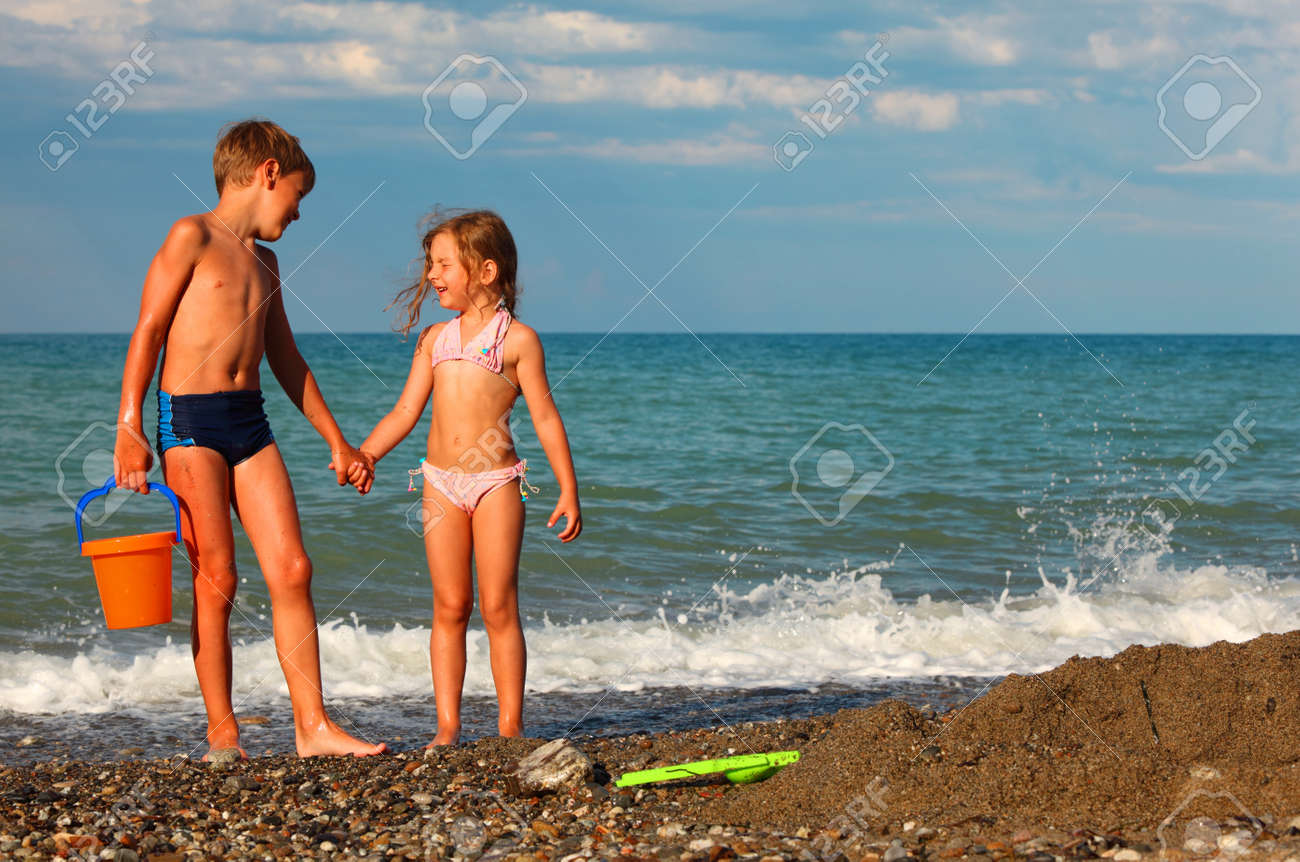 brother and sister hold hands and stand on beach. boy holding plastic orange bucket - 17723655