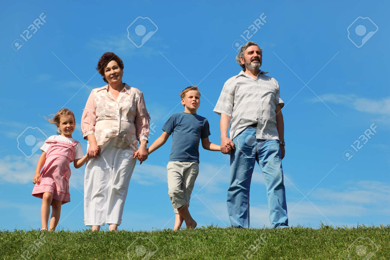 grandfather and grandmother standing on green lawn and holding for hands grandchilds Stock Photo - 17724540
