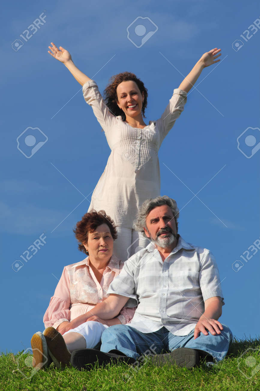 adult daughter with apart hands, her parents sitting on summer lawn Stock Photo - 17724478