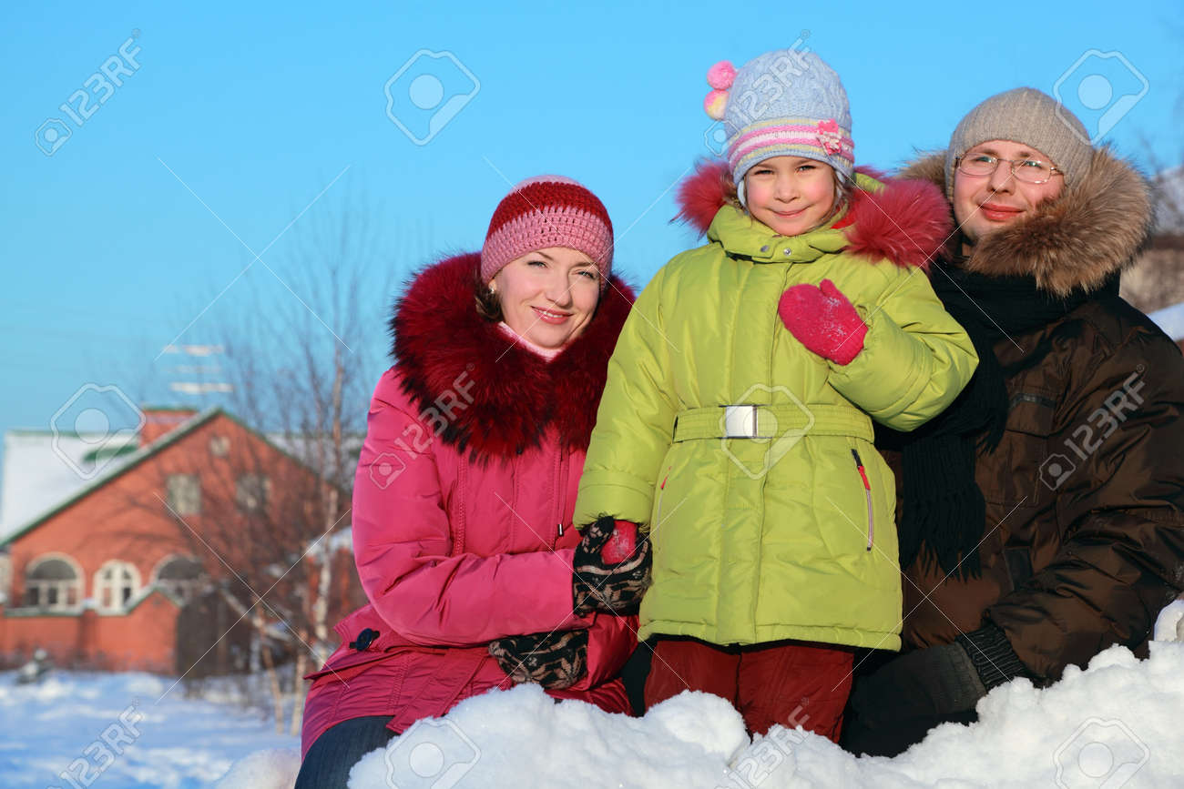 father, mother and daughter standing outdoors in winter near house, mother holding daughter hand Stock Photo - 17724315