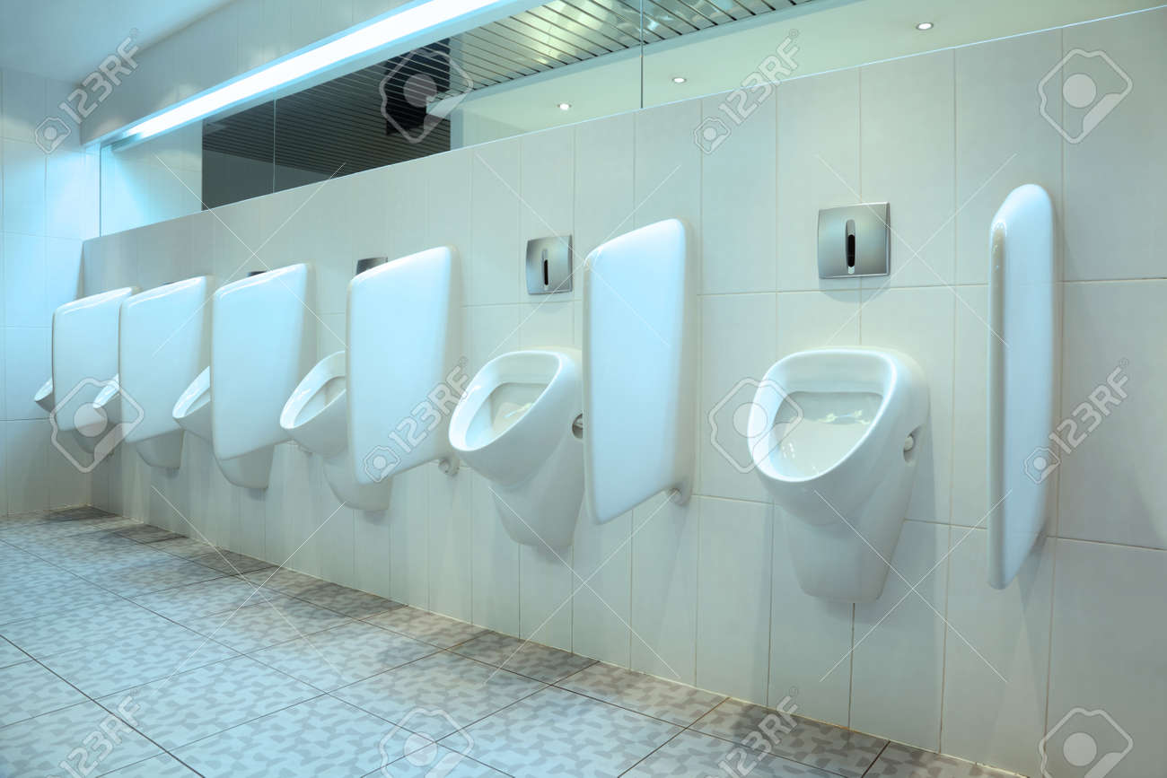 Line Of Six White Porcelain Urinals In Clean, Light Public Toilets ...