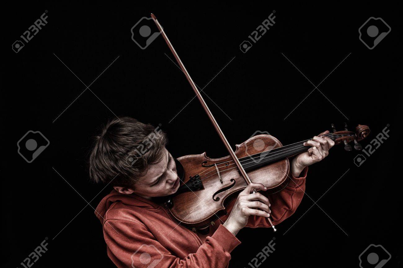 Young boy plays violin on black