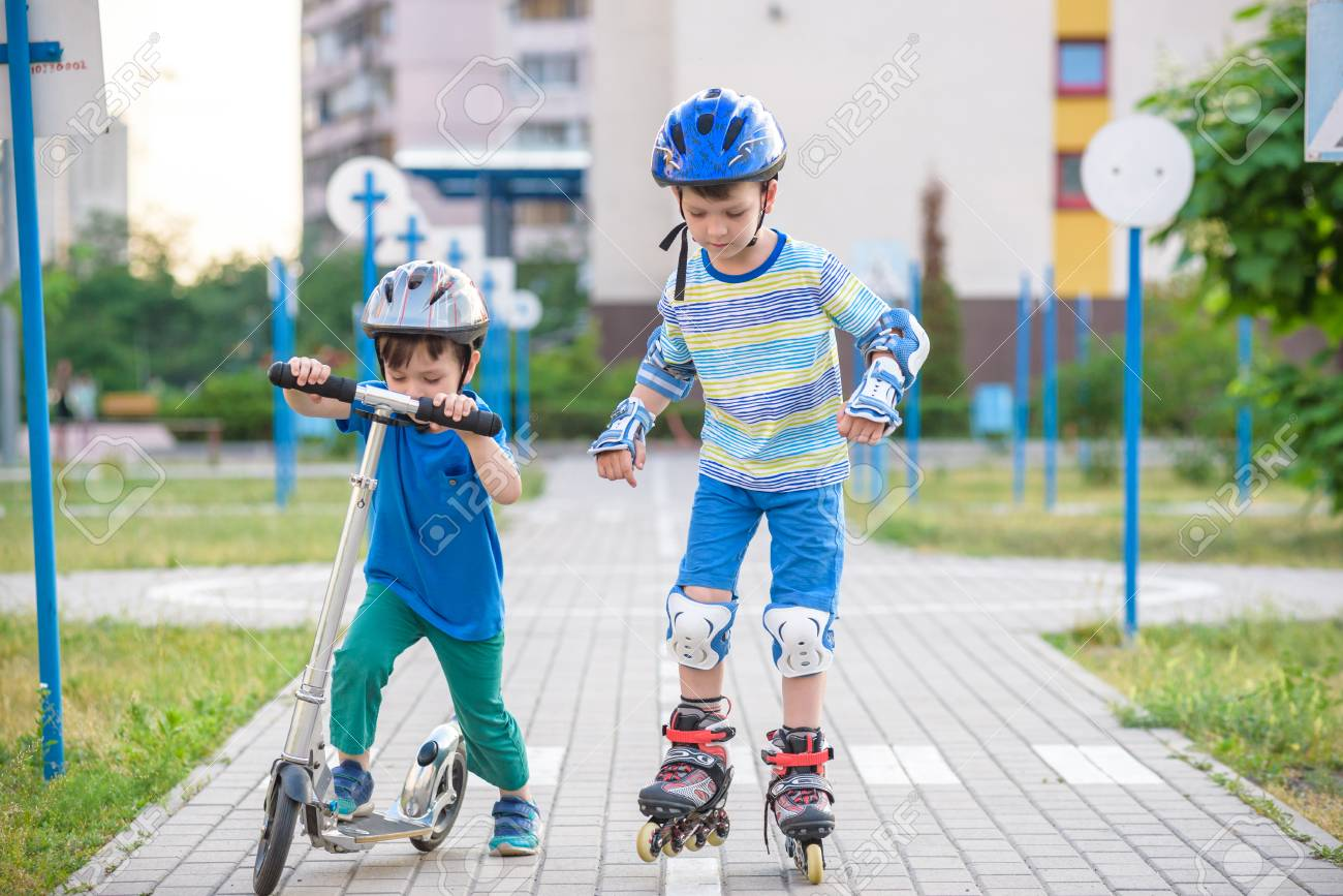 Two Kid Boy On Roller Skates And His Sibling Brother On Scooter Stock Photo Picture And Royalty Free Image Image 103796471