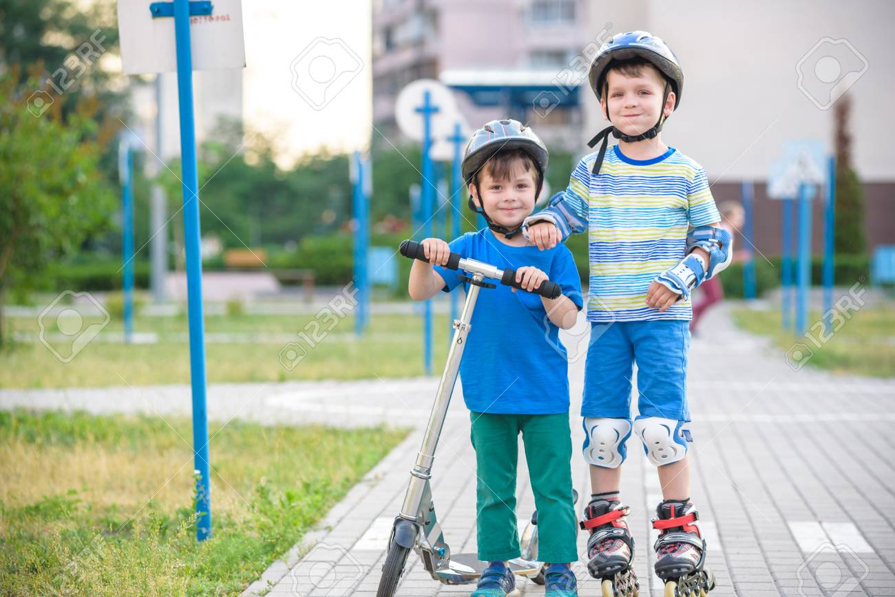 Two Kid Boy On Roller Skates And His Sibling Brother On Scooter Stock Photo Picture And Royalty Free Image Image 116371490