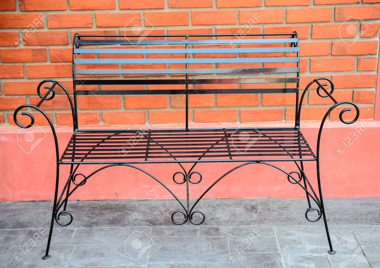 Black Metal Bench With Red Brick Wall Stock Photo   27578069