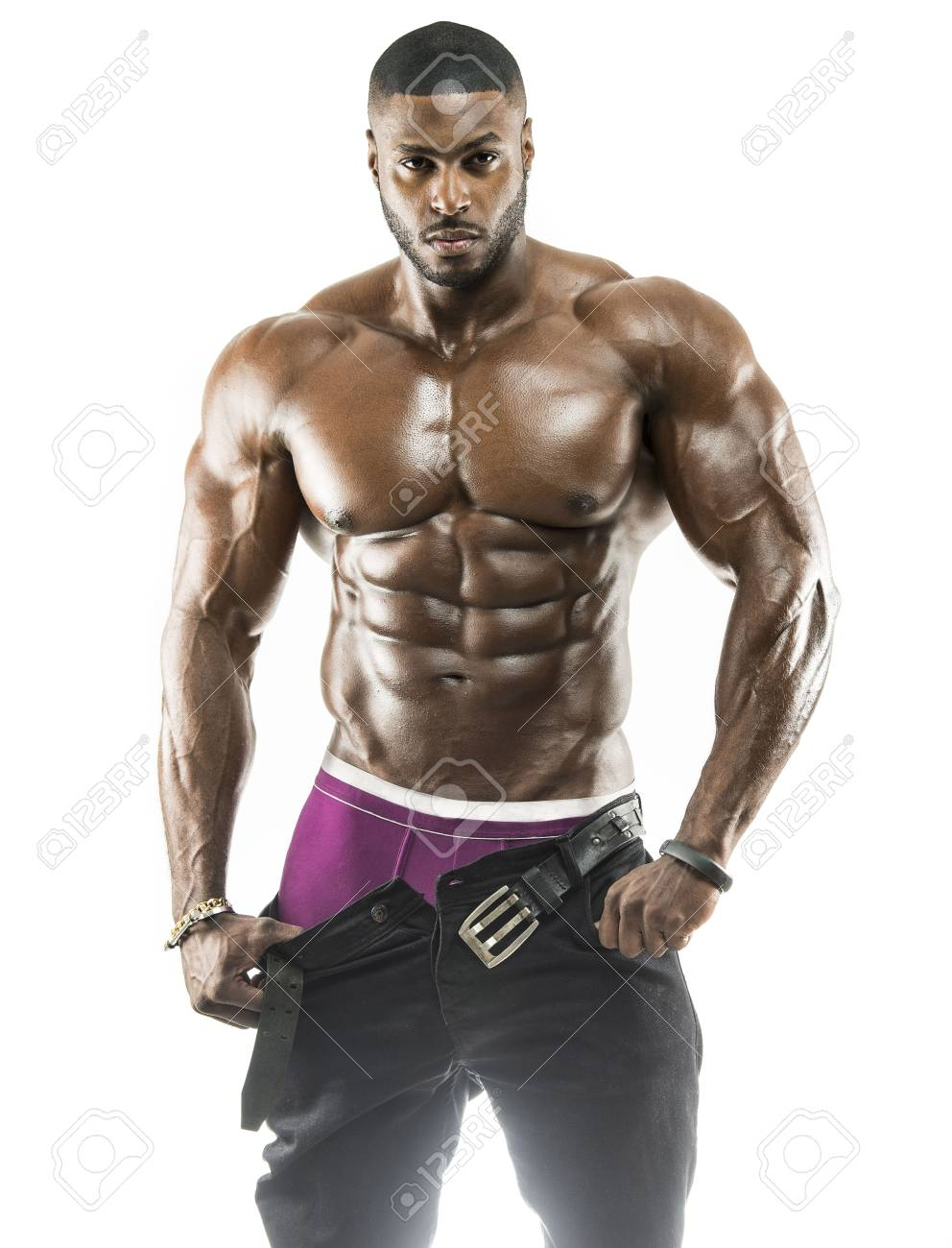 Handsome muscular Arabic Black man removing his pants showing abs and black under wear with oiled body - 99202286