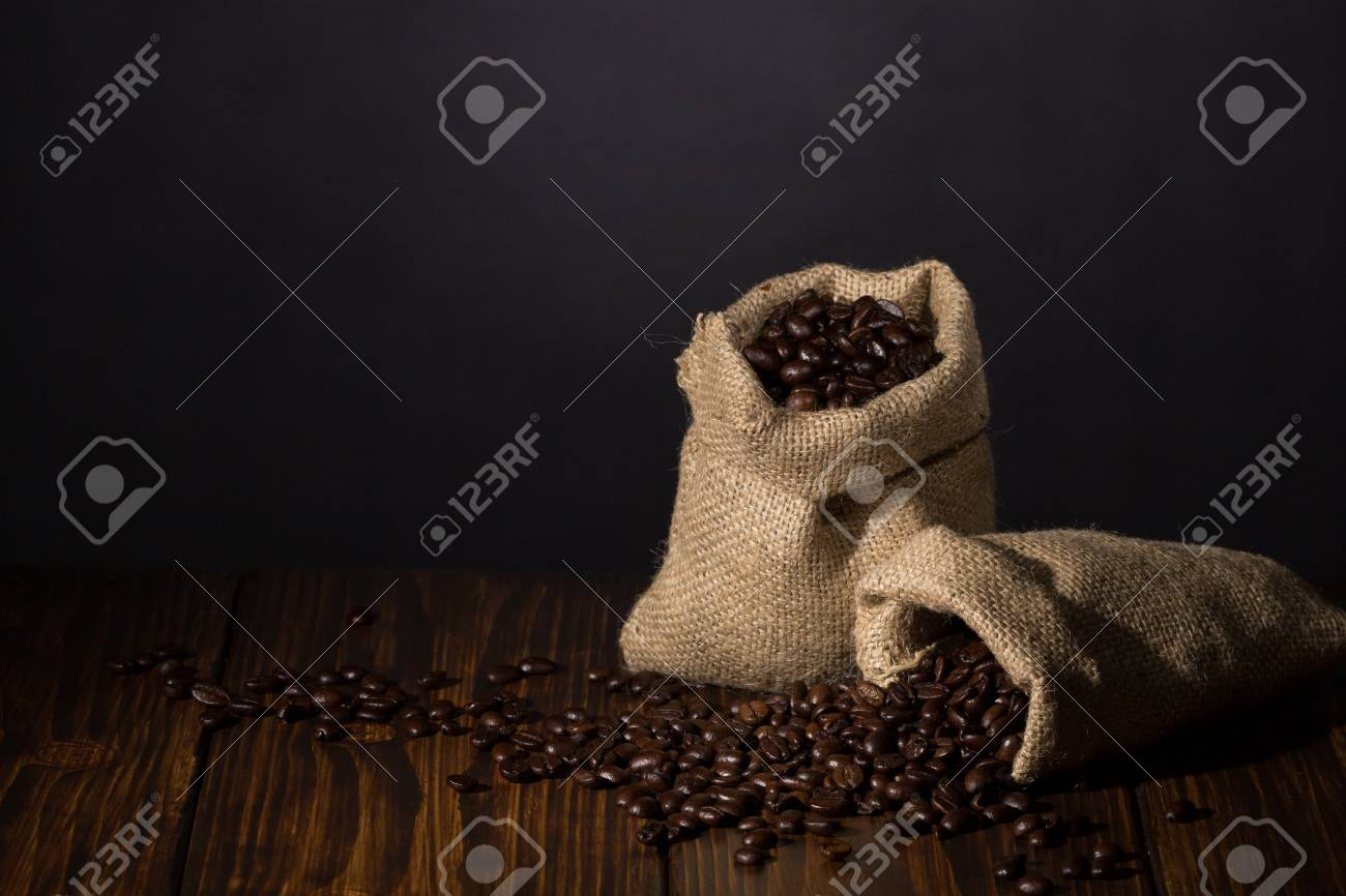 Two small sacks with coffee on wooden background Stock Photo - 20870470
