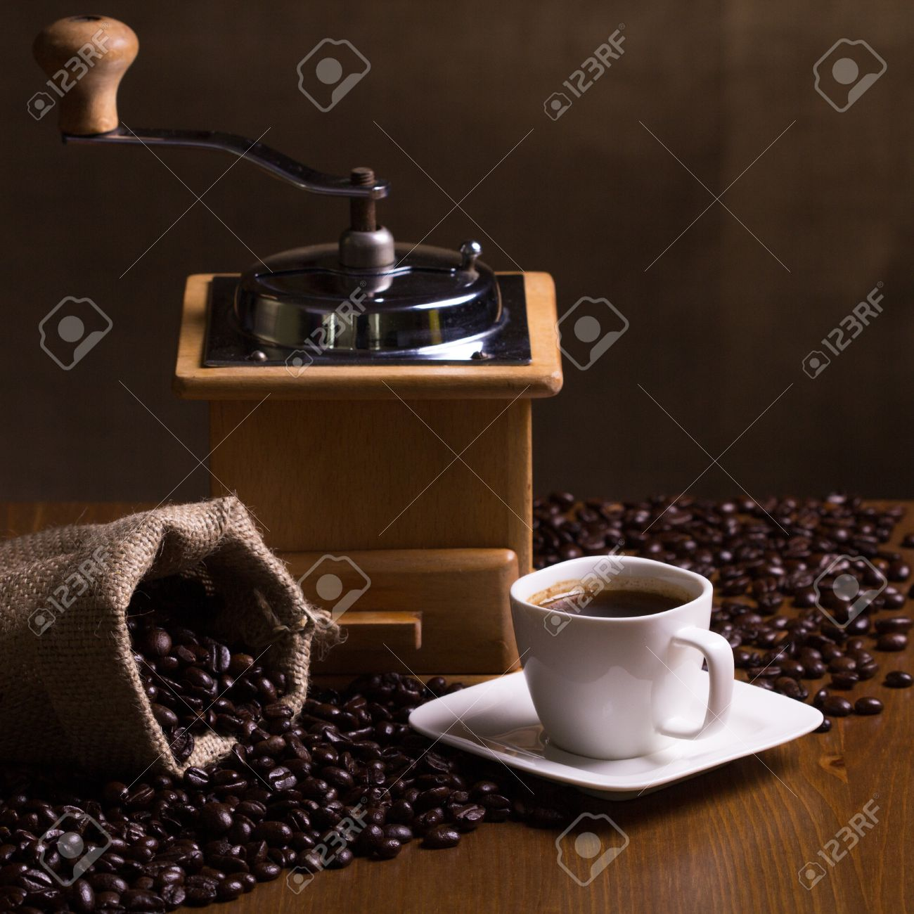 Still-life with coffee, cup with saucer, coffe mill, sac with beans and spices Stock Photo - 20870433