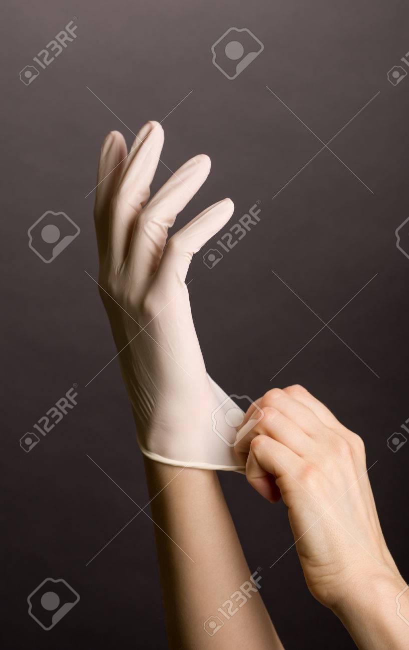Female hands putting on latex gloves on dark background