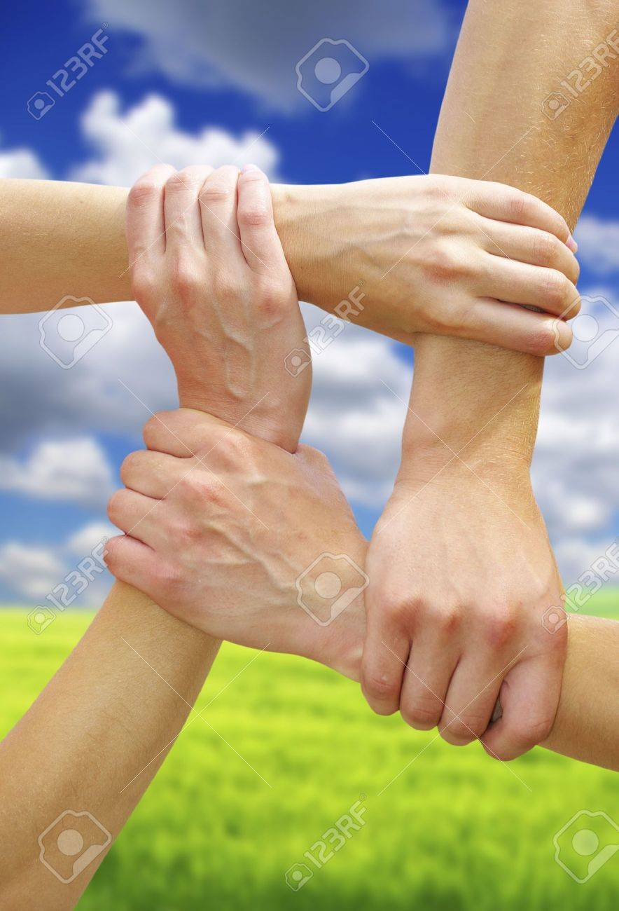 Linked hands on a sky background symbolizing teamwork and friendship Stock Photo - 5639951