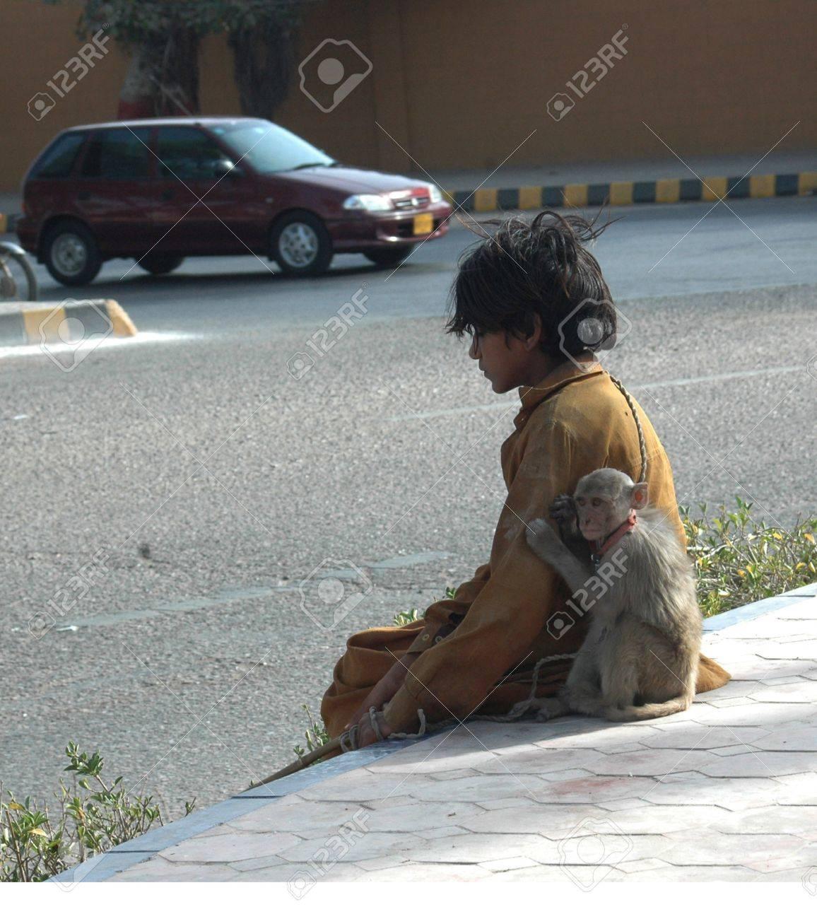 PAKISTAN_KARACHI_Young teen age boy monkey charmer he makes living to show  monkey actin to public and