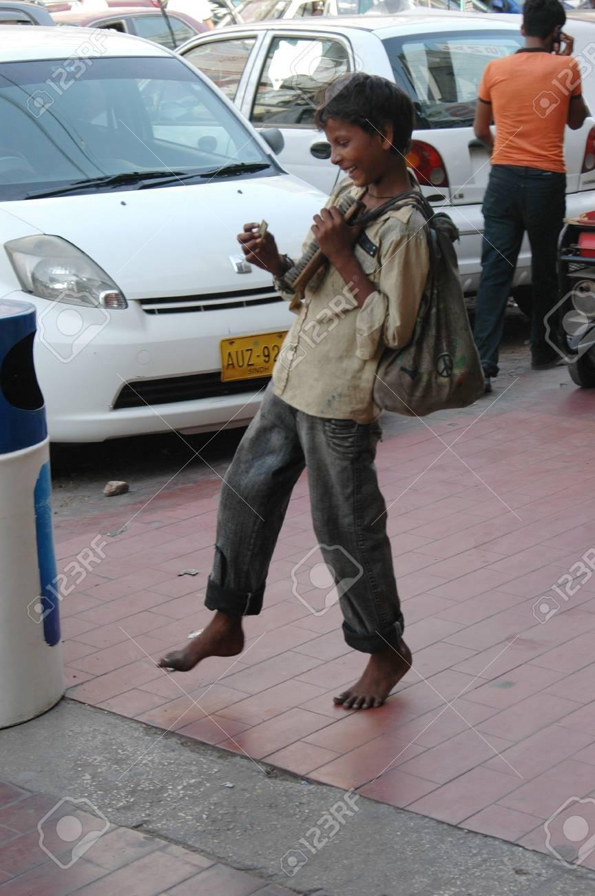 PAKISTAN_ KARACHI_a young teenager waiting for a job shoe polish