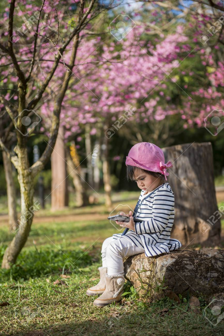 cute adorable nice baby girl sitting play smartphone under sakura