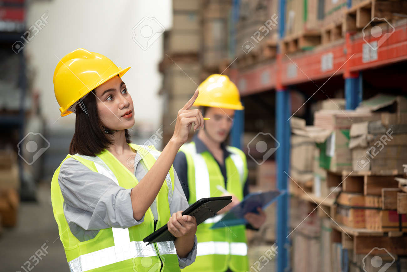 Warehouse worker checking packages on shelf in a large store - 168658036
