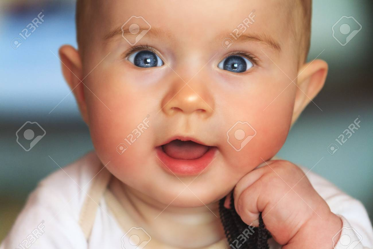 beautiful smiling cute baby girl,pink cheeks, blue eyes, open