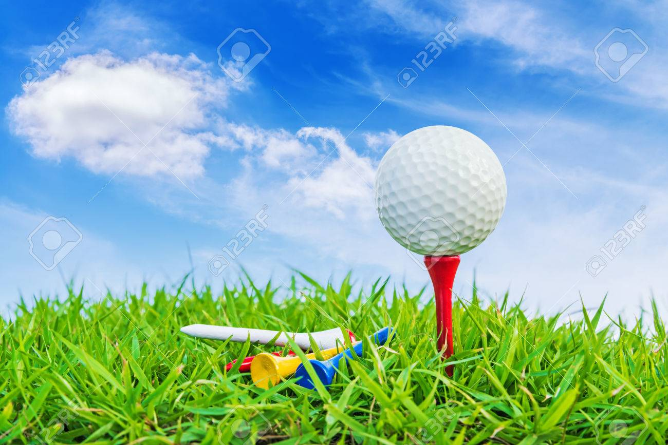Golf ball on a tee against a blue sky and white clouds. Stock Photo - 32949876