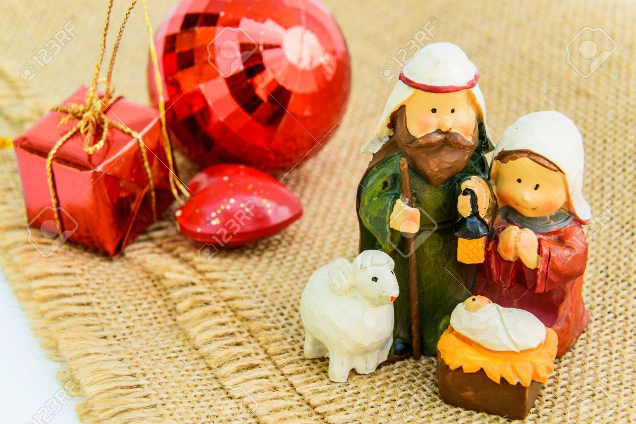 Christmas nativity scene with Mary, Joseph, and sheep looking down on baby Jesus in his manger Stock Photo - 34982491