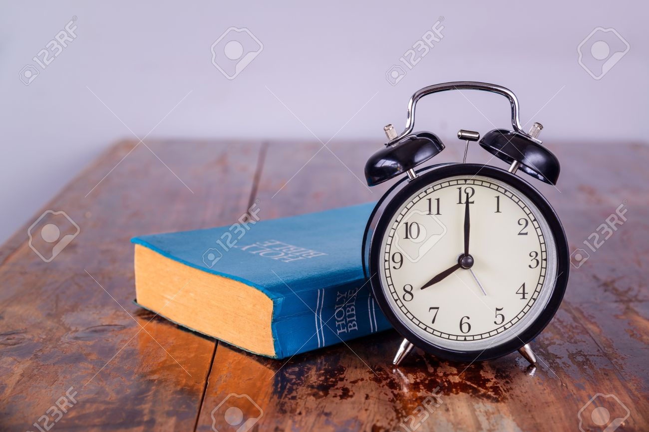 Holy bible and alarm clock on wood table. Stock Photo - 45125676