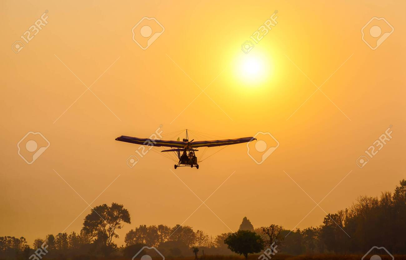 Ultralight trike flying with a pilot and a passenger against sunset sky, A microlight aircraft with two passengers with the sun - 141181297