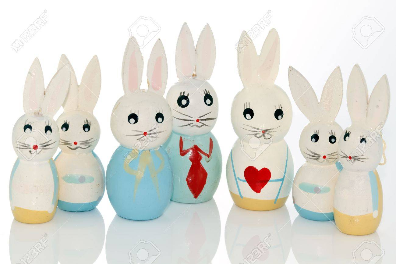 wooden easter bunnies in a row on a white reflecting background Stock Photo - 6358173