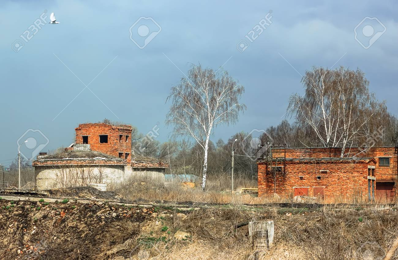 spring landscape with abandoned destroyed technical brick buildings