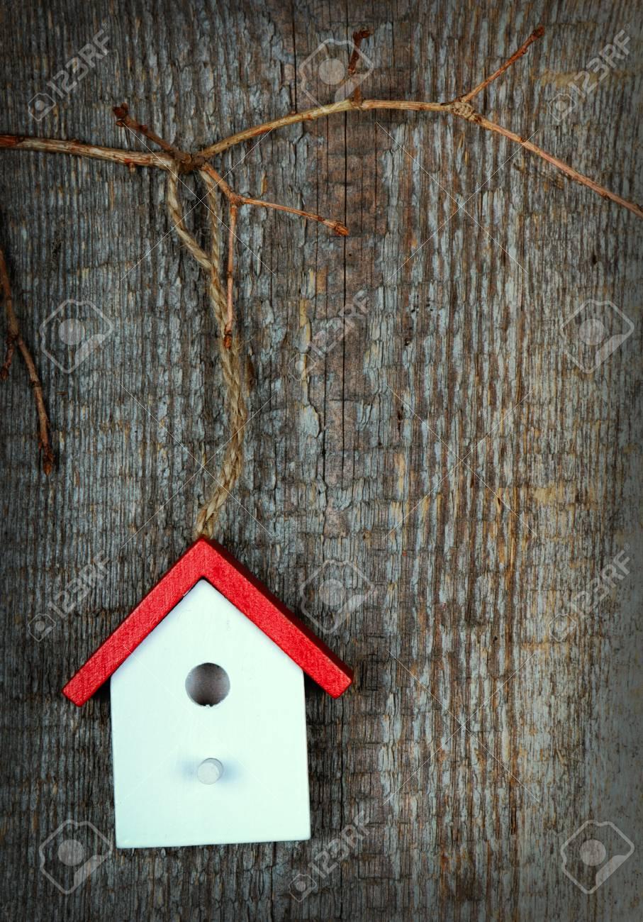 Foto de archivo - Una casa para pájaros pintados con los colores rojo y  blanco sobre fondo de madera vieja 064c0850748