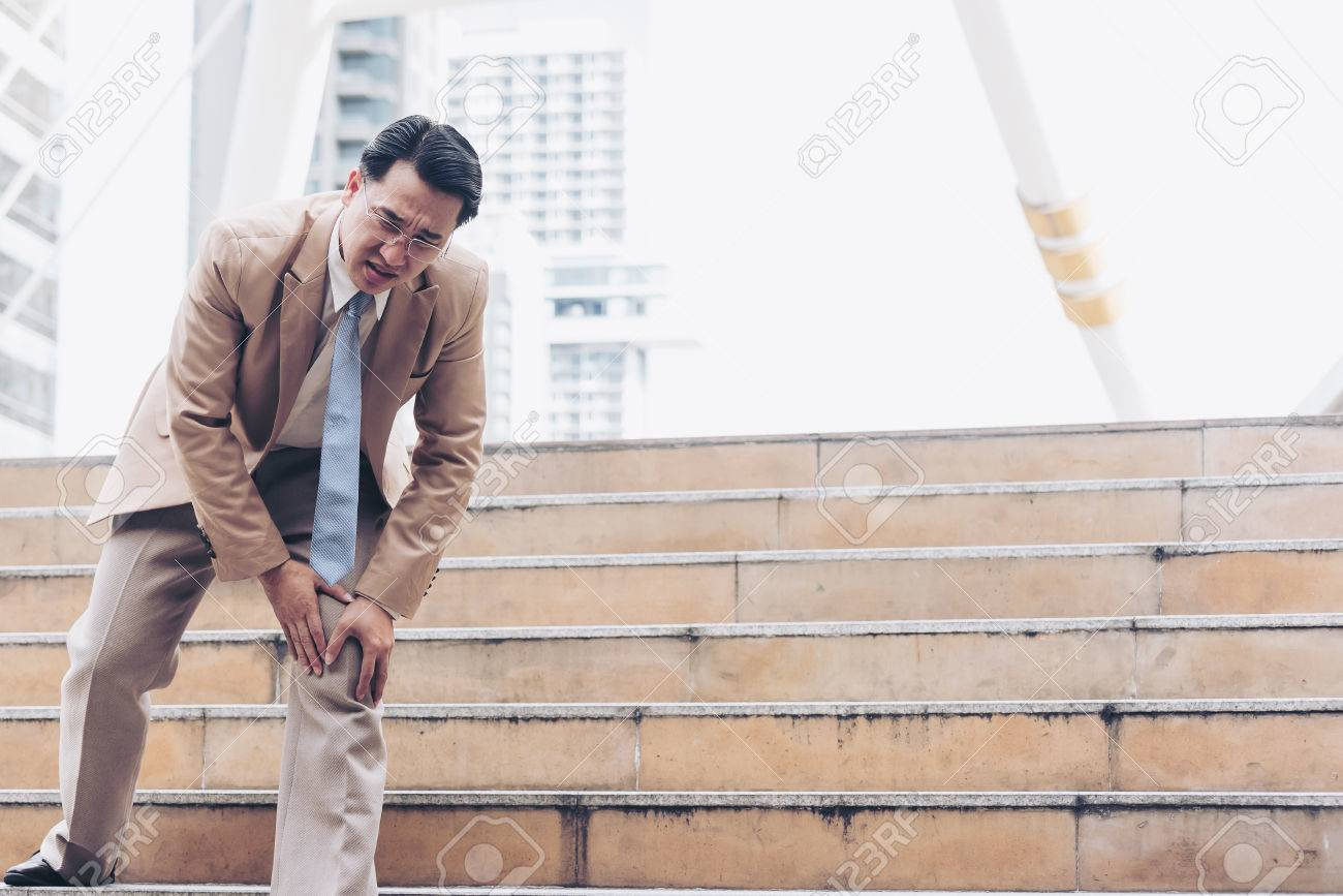 Businessman have the pain and painful knee expression and sit down on the stairs during go to office - 80884446