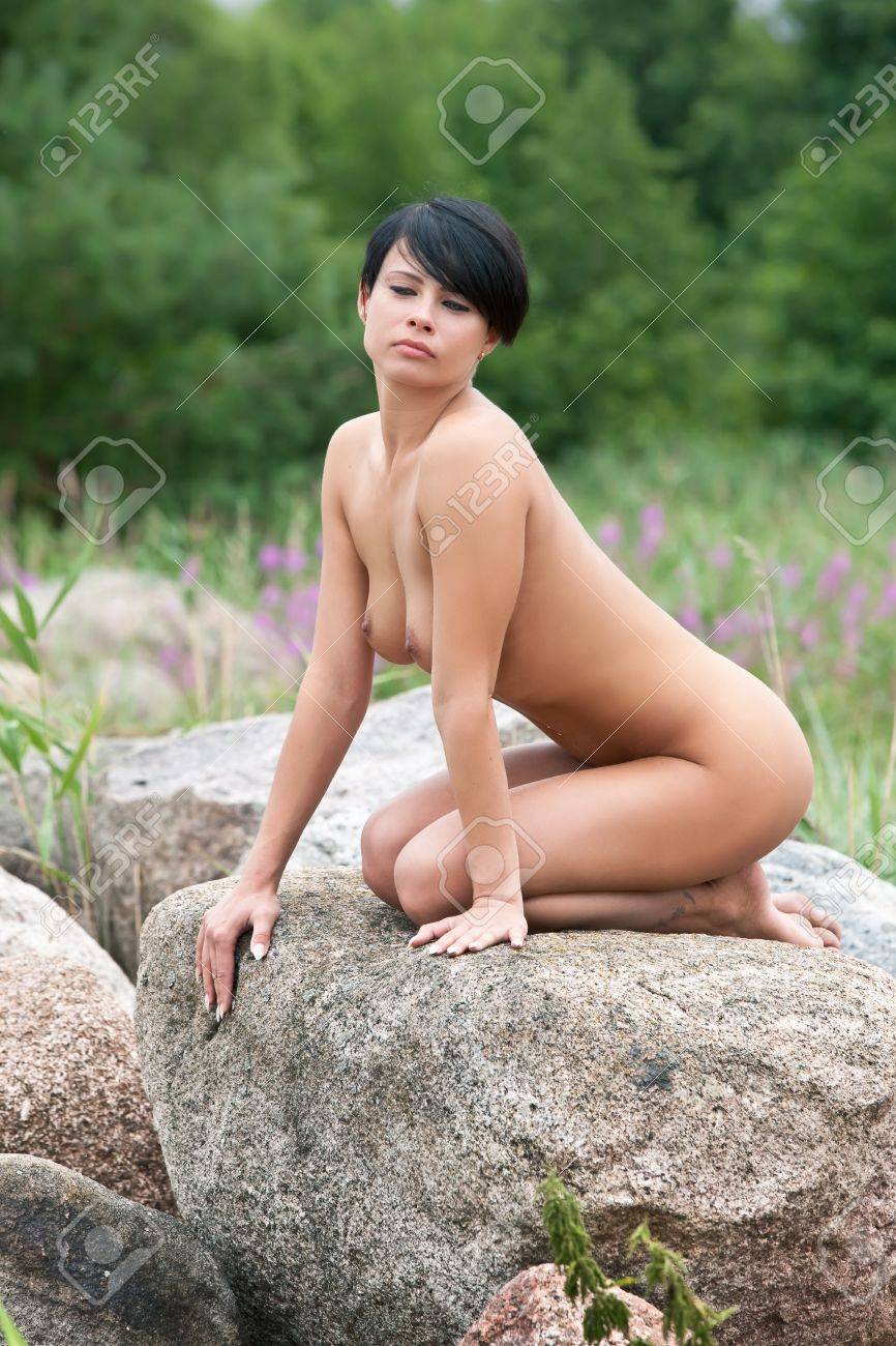 Beautiful nude woman sitting on the stone against nature background Stock Photo - 12419264