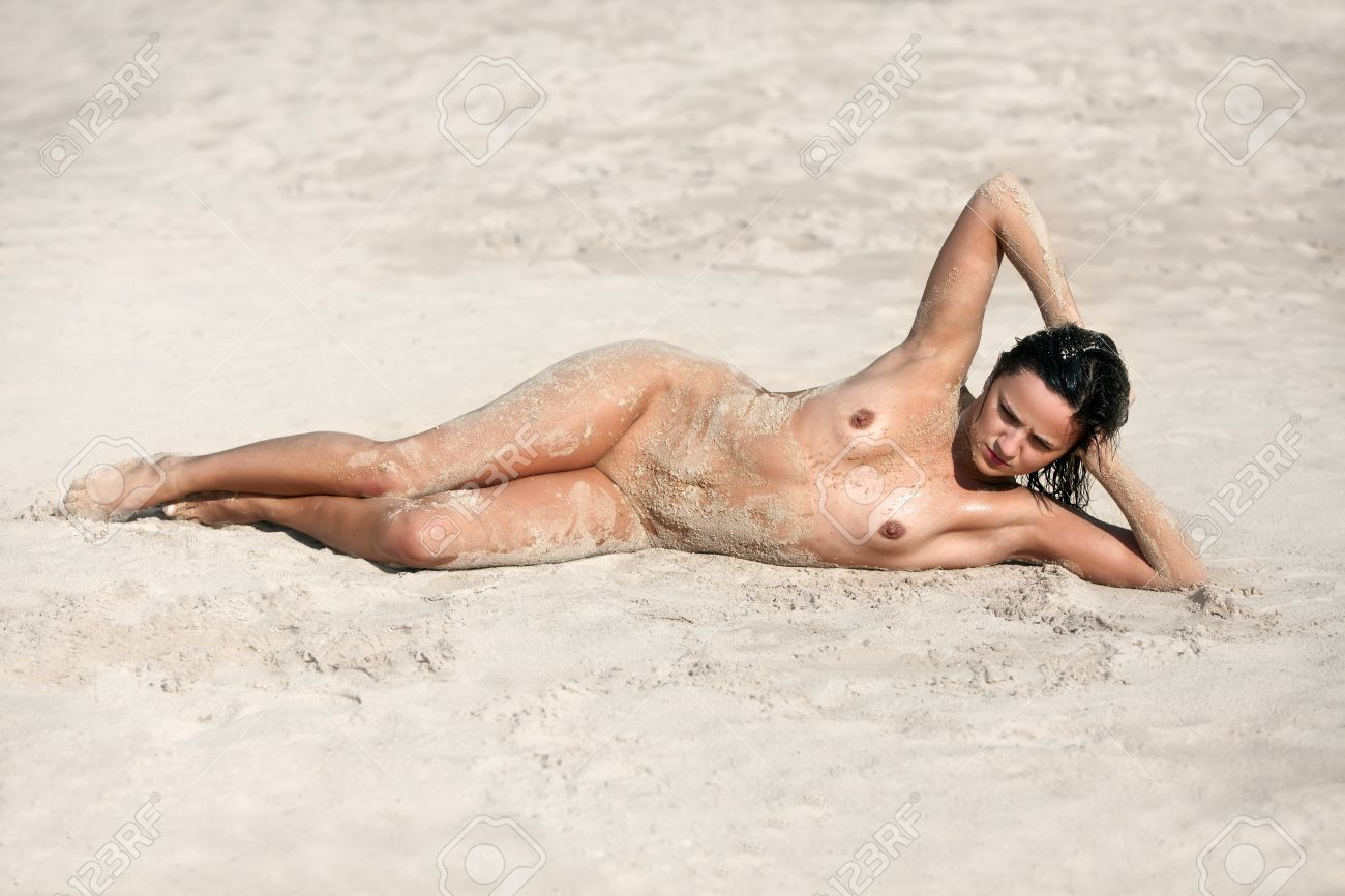 sand naked Stock Photo - Young wet nude woman lying on the sand