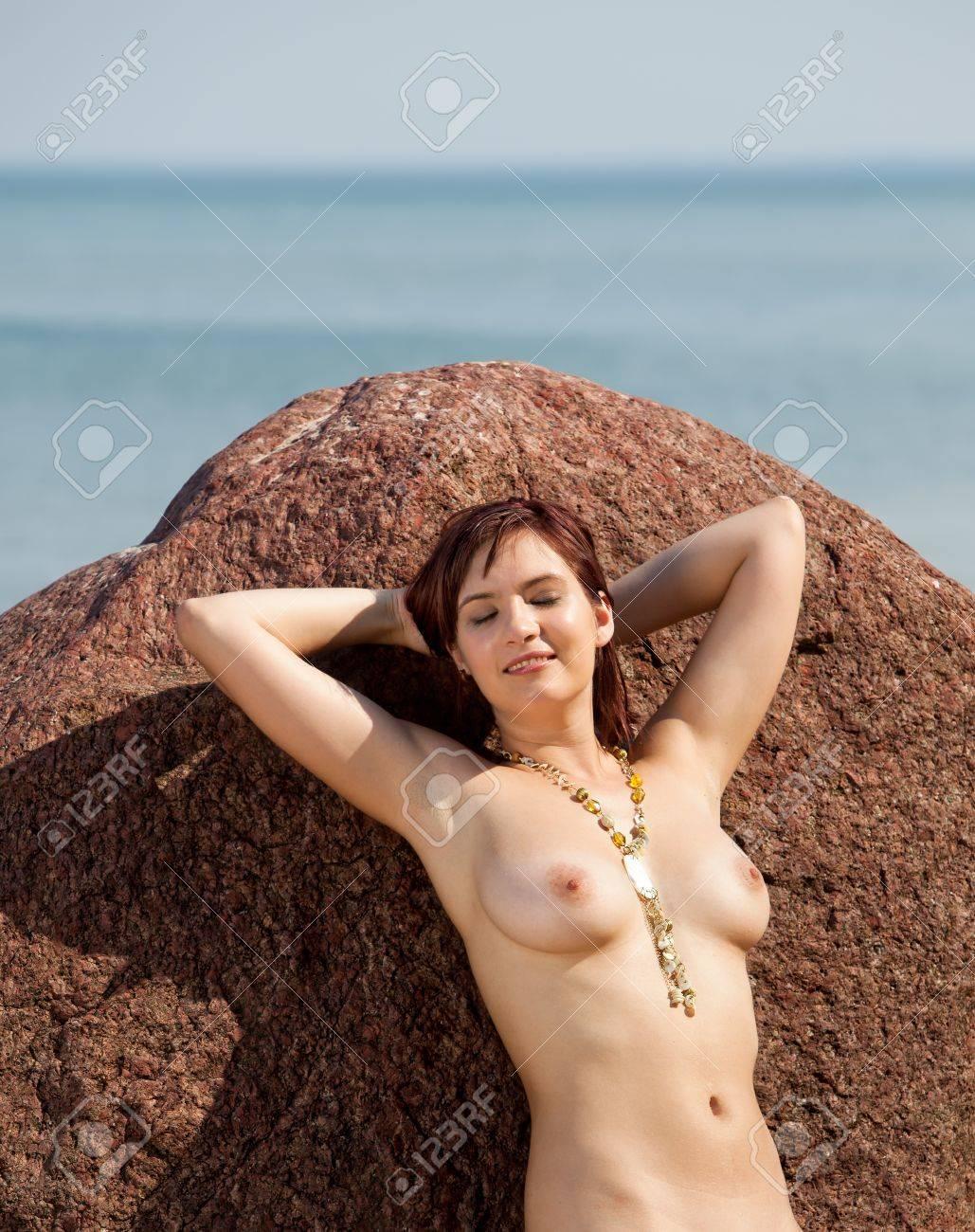 Young naked woman sunbathing near the stone on sea background Stock Photo - 12913939