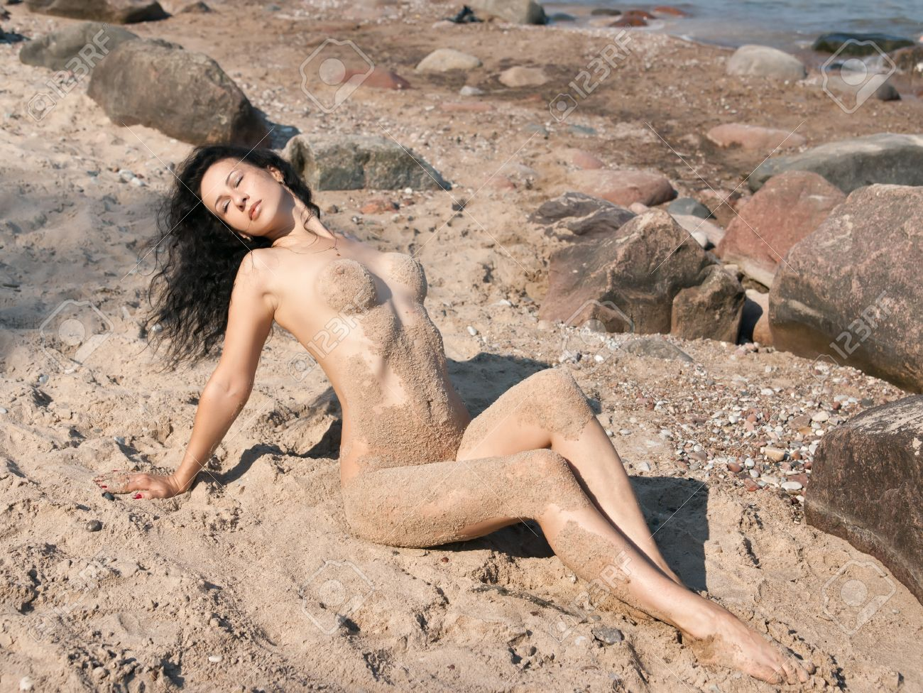 sand naked Stock Photo - Young wet nude woman covered by sand lying on the beach
