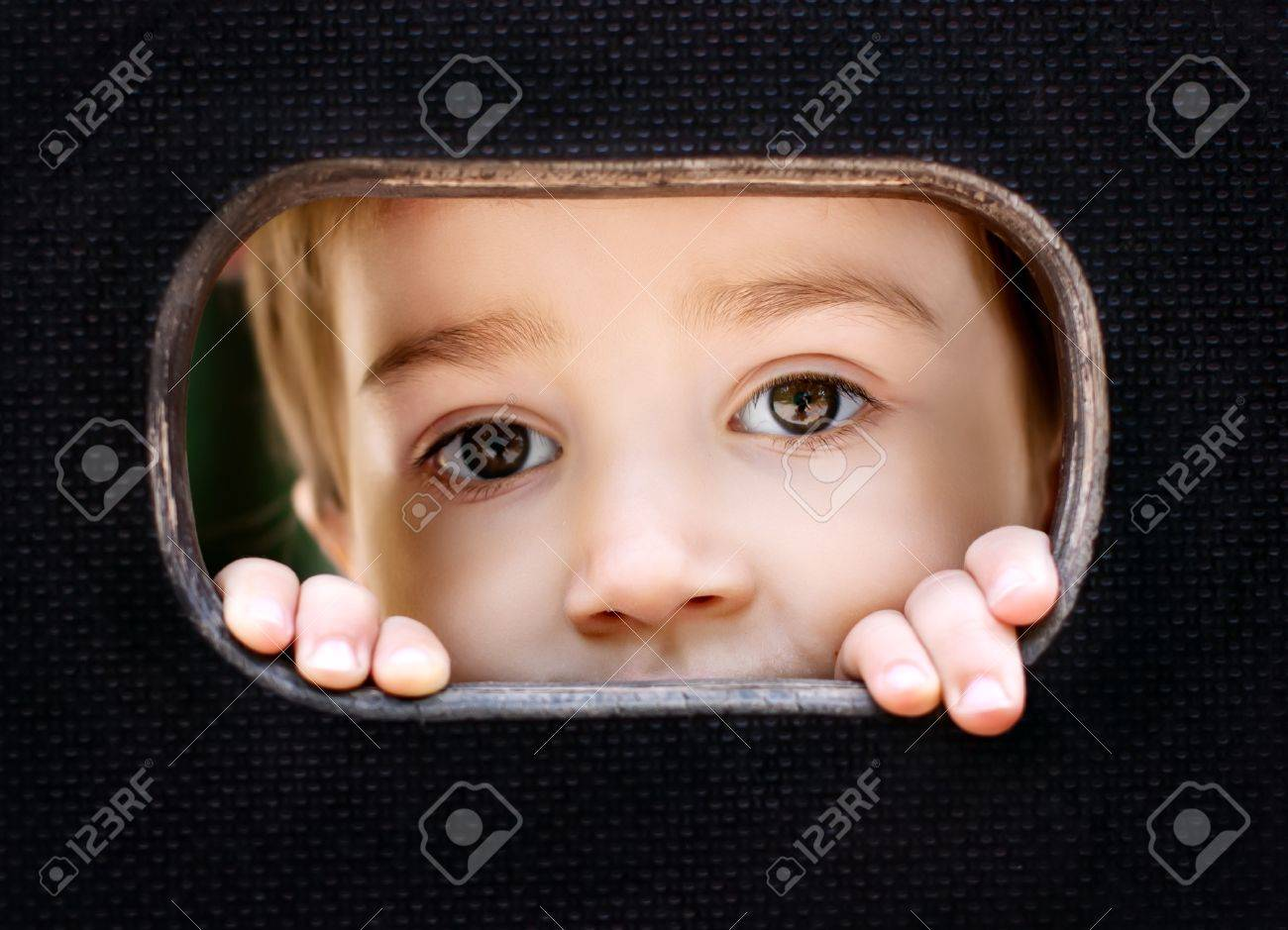 Curious kid spying through the hole in the wooden wall on playground Stock Photo - 14343600