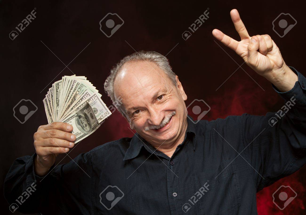 Lucky old man holding group of dollar bills and fingers in victory sign Stock Photo - 15783245