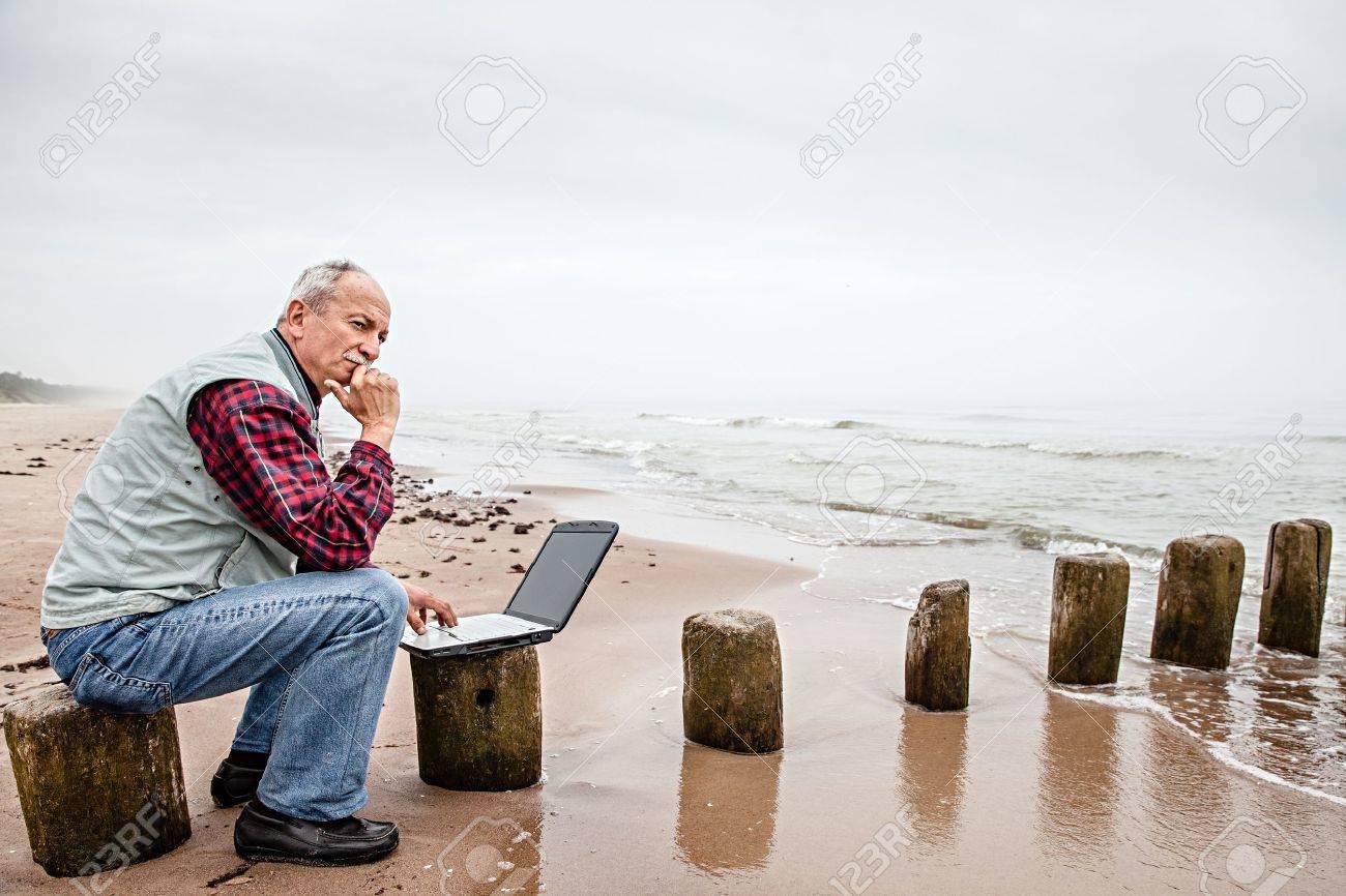 Senior businessman on beach working with notebook Stock Photo - 21361877