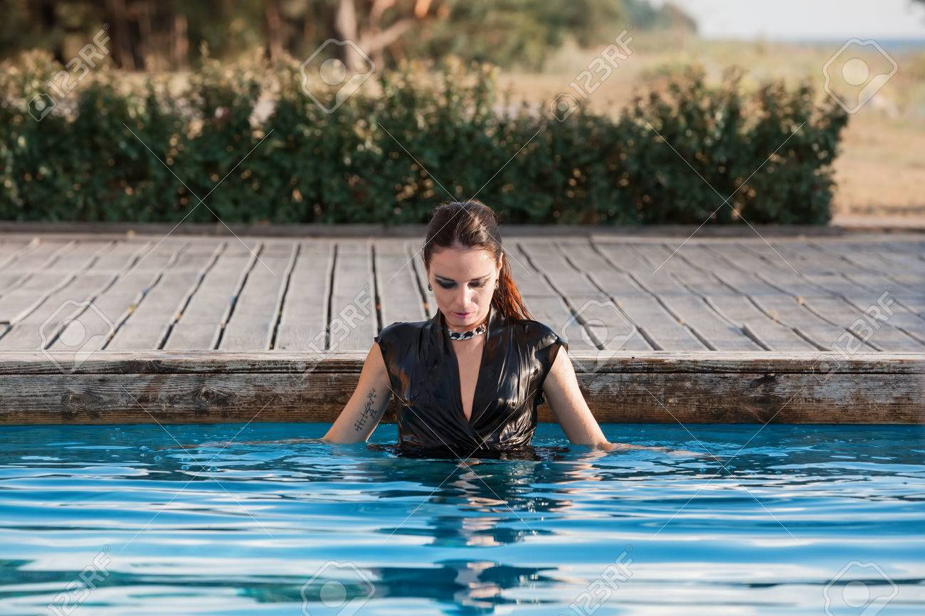 bda1ca6b91f7c Stylish young wet woman in black dress standing in the water in a swimming  pool Stock