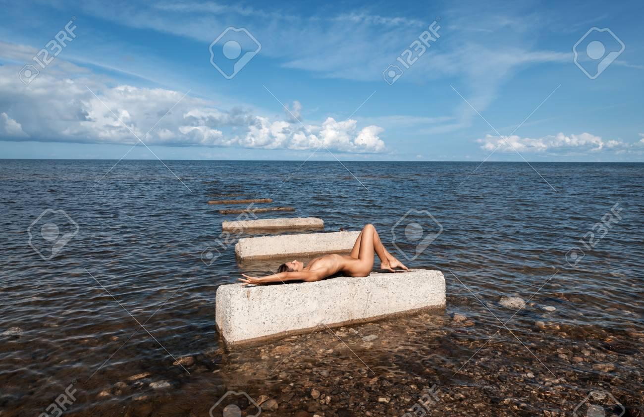 Joven Mujer Desnuda En Un Día Soleado De Verano Tomando El Sol En Las Losas De Hormigón Que Se Encuentran En El Mar