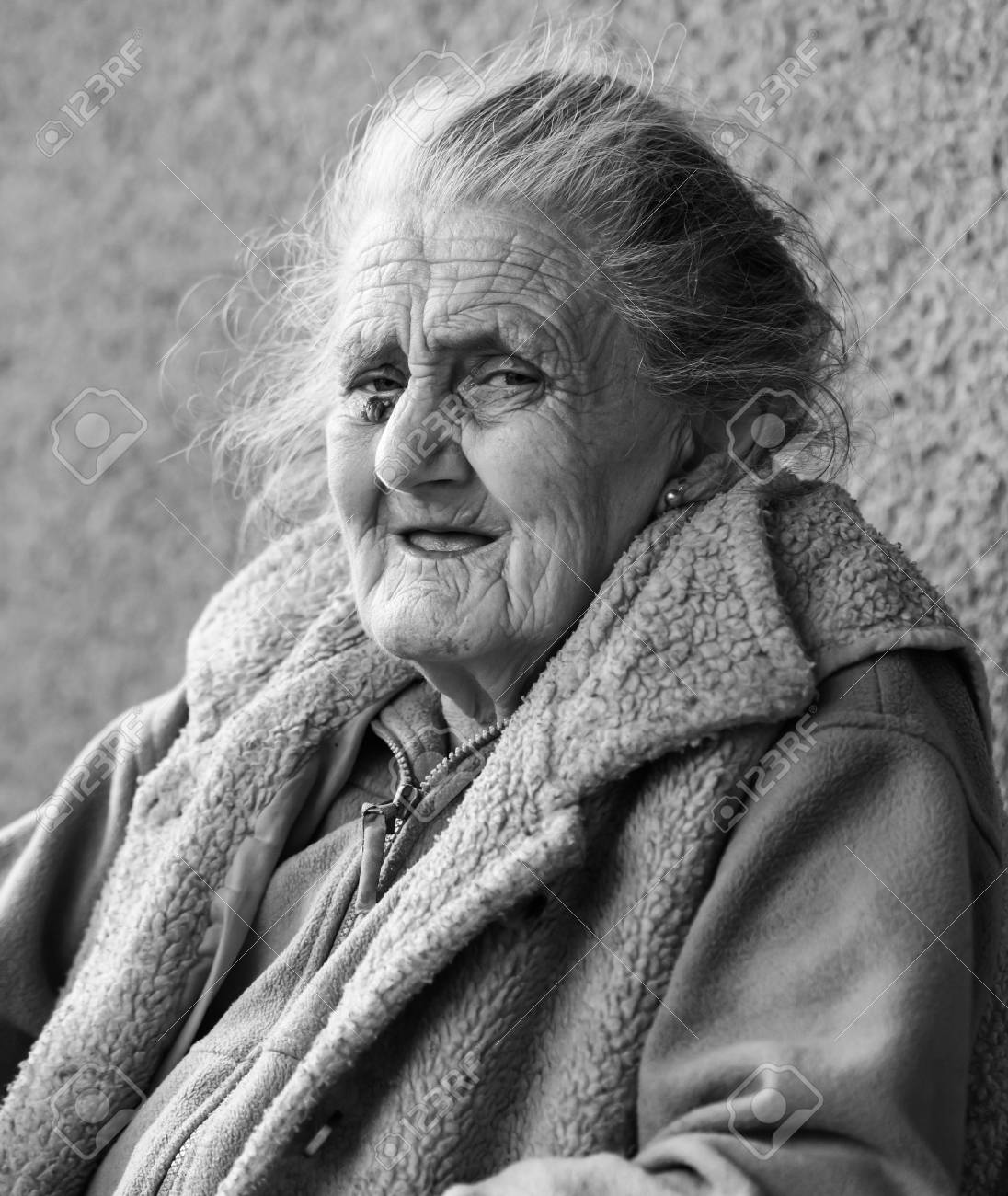 Old age and lifestyle concept black and white portrait of a very old and tired wrinkled woman outdoors very old hoary woman face closeup portrait